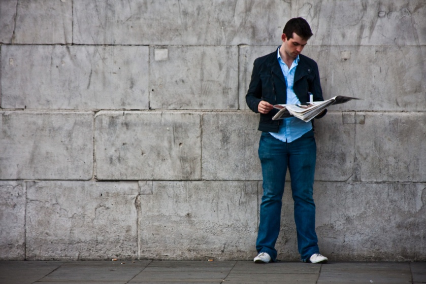 A man reads a newspaper by the wall.