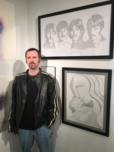 Dennis Wells stands before some of his larger works on display at Delurk Gallery (Photo: Pat Berryhill)